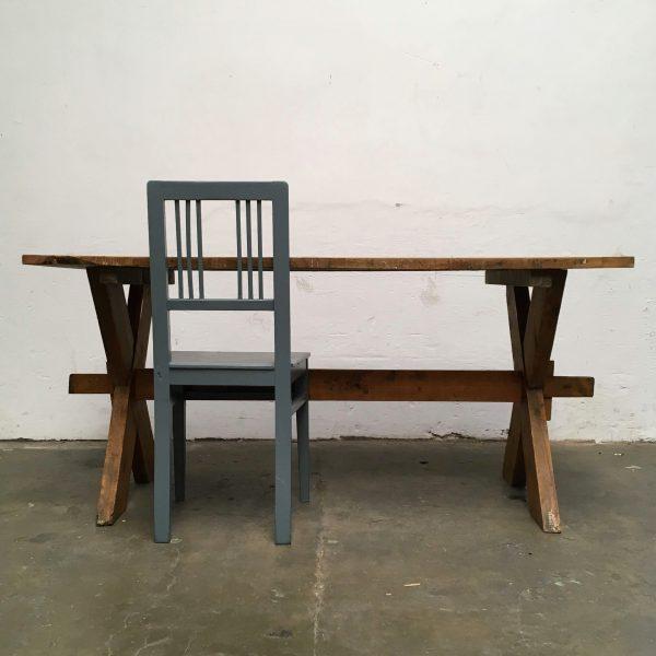 Industriële houten kruispoot tafel met grijze stoel.