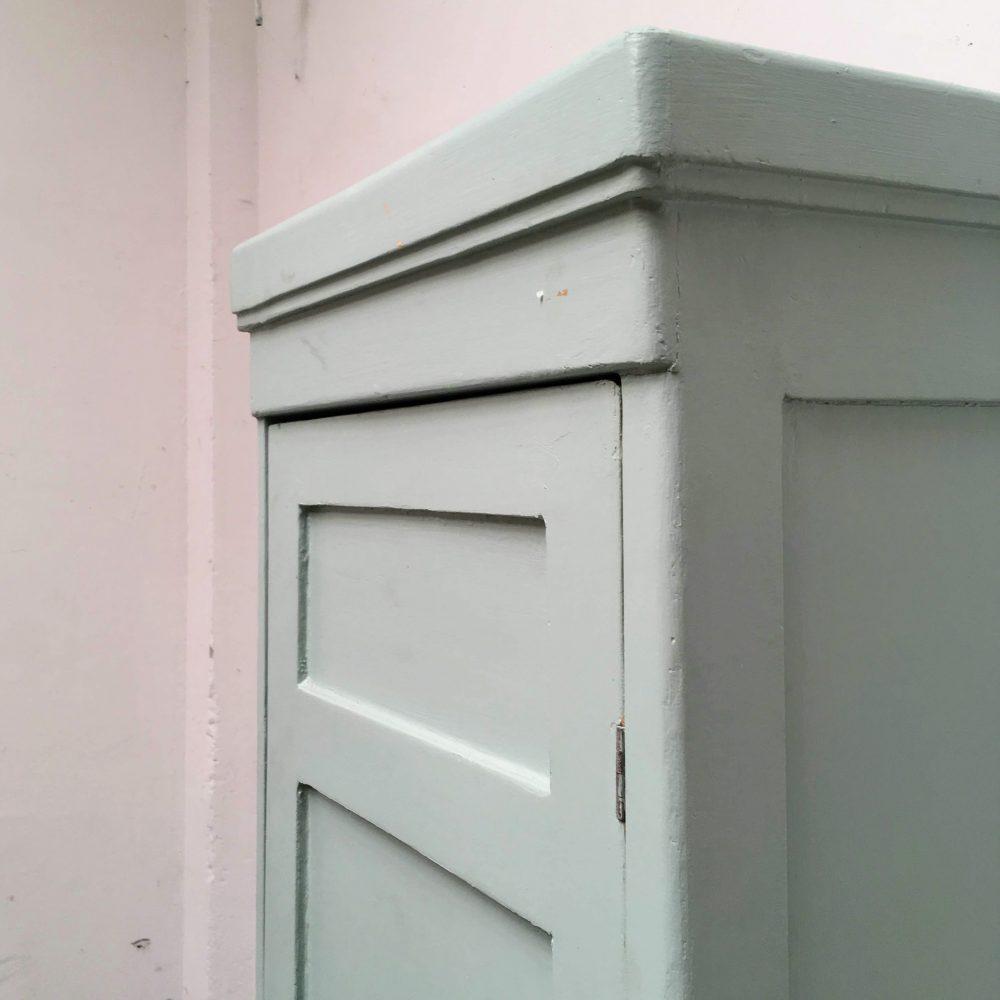 Bovenkant van blauwe houten 1-deurs kast.