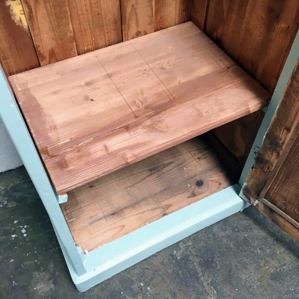 Plank binnenin blauwe houten 1-deurs kast.