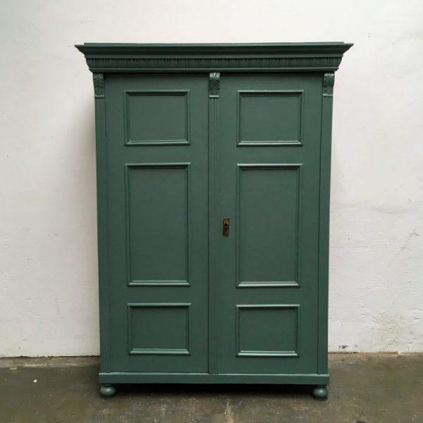 Een donkergroene houten twee deuren kast.