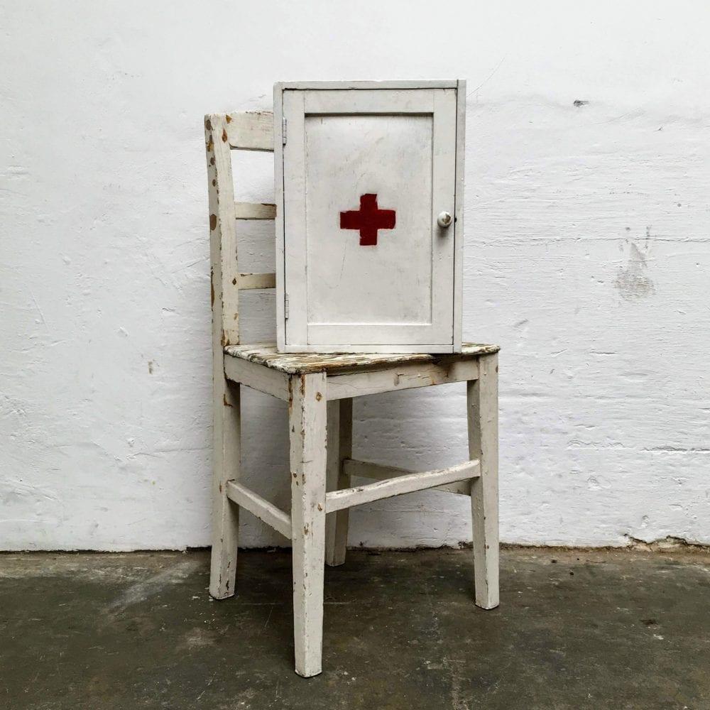Wit houten medicijnkastje op stoel
